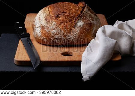 Artisan Sourdough Bread. Freshly Baked Round Loaf Of Sourdough Bread With Linen Cloth And Knife On B