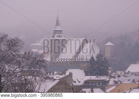 Black Church In Brasov Seen Through Fog And Snowflakes, Transylvania, Romania
