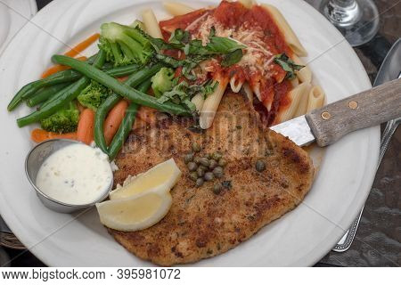 A White Plate With Calamari Steak, Pasta With Pomodoro Sauce And Sauté Vegetables, Viewed From Above