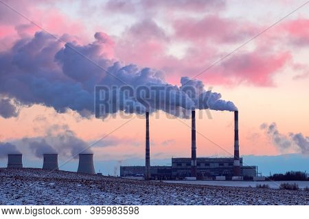 Thermal Power Plant In The Cold Winter Landscape. Pipe With Smoke Against The Pink Sunset Sky