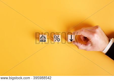 Symbols House, Percent And Down Arrow On Wooden Cubes And Orange Background. Concept Of Low Cost Rea