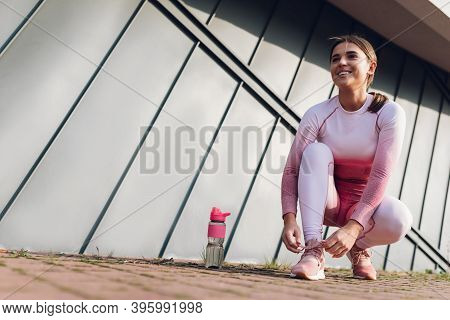 Young Fitness Woman Tying Shoelaces. Sport Woman