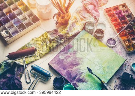 Artistic Equipment: Canvas And Palette Knife, Paint Brushes, Multicolored Paints In Artist Studio. T