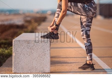 Close Up Of Sporty Caucasian Woman Runner Tying Shoelaces. Preparing For A Run