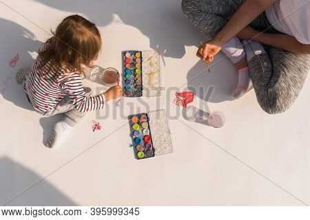 Focused Child With Mother Painting With Poster Paint Outdoors On The Ground On Big Sheet Of Paper. C