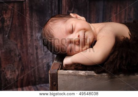 Smiling Newborn Baby Boy Sleeping In A Rustic Crate