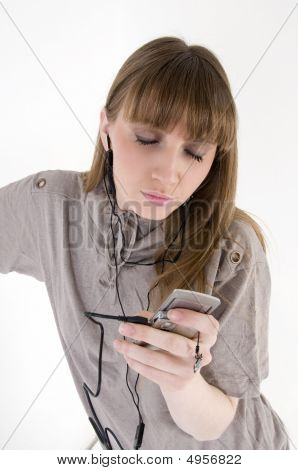 Pretty Female Model With Cellphone And Headphones