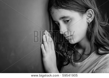 Grunge black and white portrait of a sad girl leaning against a wall