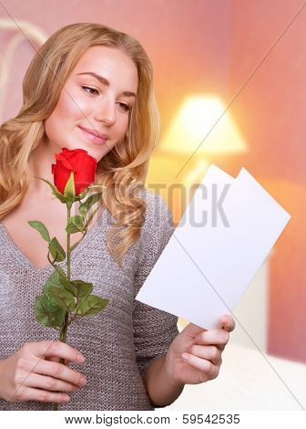 Portrait of cute blonde girl reading love letter with red rose in hand at home, receive festive postcard from lovers in Valentine's day