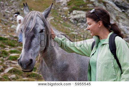 a young woman is petting a horse in the mountains poster