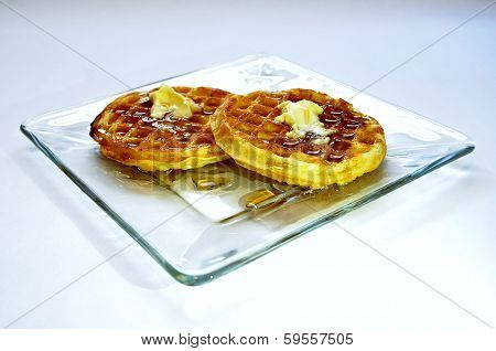 Waffles With Butter And Syrup On Glass Plate