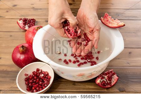 Hands collecting pomegranate seeds in a bowl of water for making juice