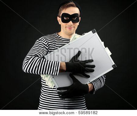 Thief with metal briefcase on dark background