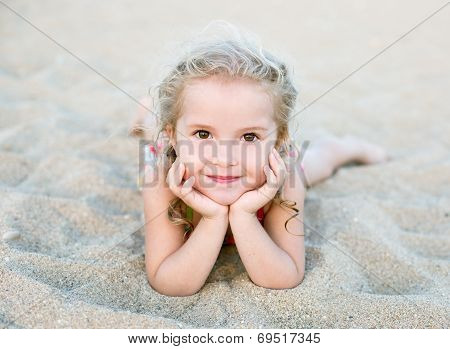 Happy Little Girl Lying On The Sand