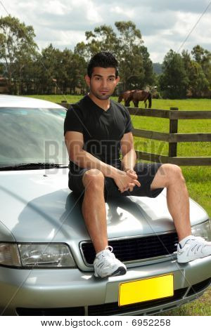 Man Sitting On Bonnet Of Silver Car In Countryside