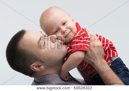 Young handsome father kissing his toddler son