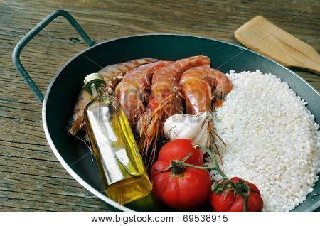 ingredients to prepare a spanish paella or arroz negro on a rustic wooden table