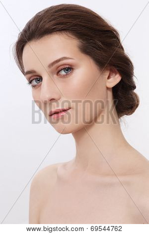 Portrait of young attractive woman with hair bun and clean make-up