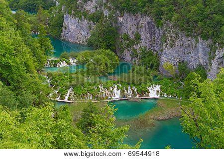 Plitvice Lakes: People Walking On A Footbridge Over Water