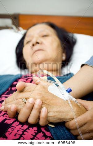 Familie Holding hände in Krankheit