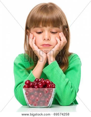 Cute girl doesn't want to eat cherries, isolated over white