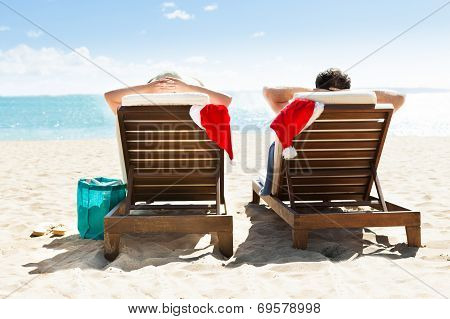 Couple With Santa Hats Relaxing On Deck Chairs At Beach Resort