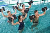 Happy fitness class doing aqua aerobics with foam dumbbells in swimming pool at the leisure centre poster