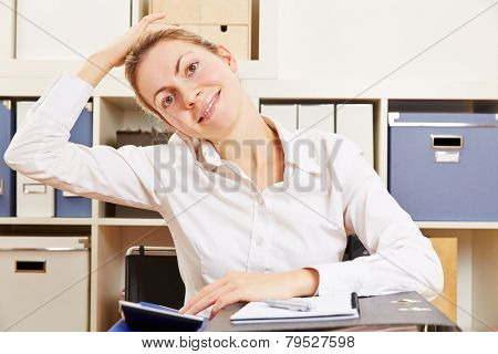 Business woman stretching her tense nape in the office