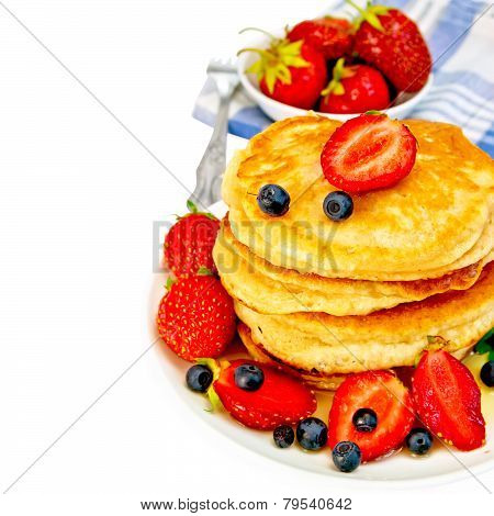 Flapjacks with strawberries and blueberries in bowl with napkin