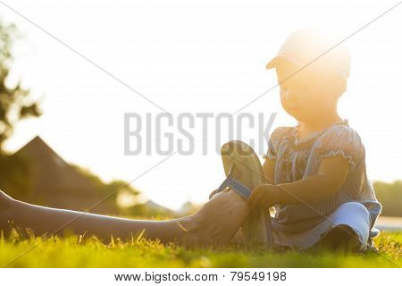 Little Girl Sitting On The Grass And Putting Flip Flips On Mother Leg On Sunny Day