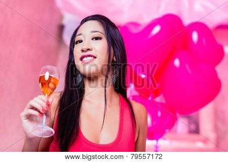 Beautiful woman drinking champagne in discotheque