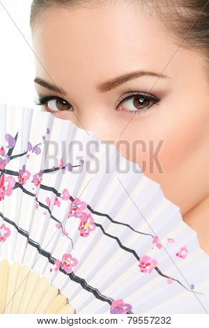 Asian beauty - seductive eyes woman chinese or japanese. Eye makeup Asian look with paper fan. Beauty portrait of mixed race Asian / Caucasian female model on white background. Close up on eyes.