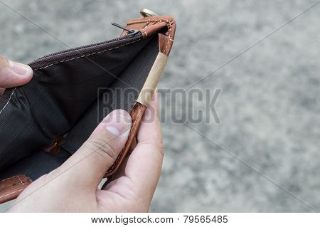 Broke Man Showing His Brown Leather Wallet With No Money