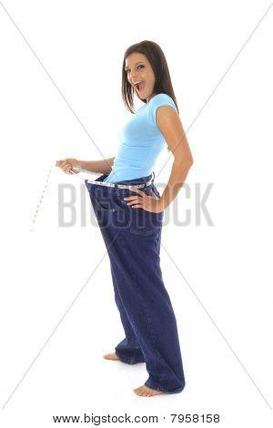 美丽的女人炫耀她在牛仔裤的重量损失