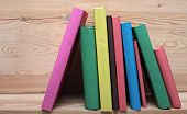 multicolored Books on wooden shelf close-up. No labels, blank spine. poster