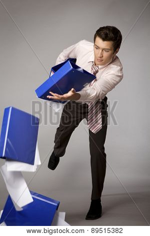 Young caucasian businessman droping a stack of binders - failure