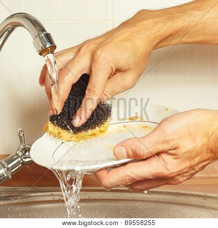 Hands wash the dirty plate under running water in kitchen