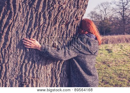 Young Woman Hugging A Big Tree In Winter