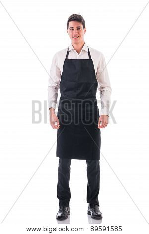 Full length shot of young chef or waiter posing, wearing black apron and white shirt isolated on white background poster