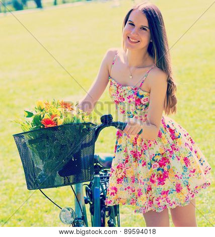 Young woman in short colorful dress with long hair rides a bicycle with basket and flowers tour summer city park, look and smile to camera. Toned Photo