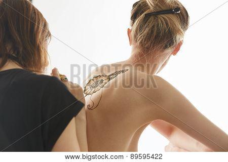 Art of mehendi. Master works on naked model, isolated over white background poster