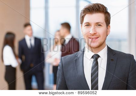 Young business man standing in front of his co-workers  talking
