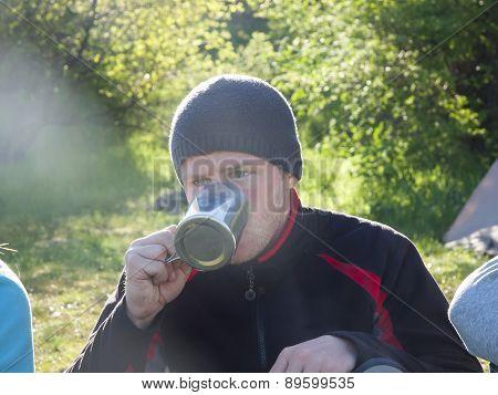 Man Drinking From A Mug.