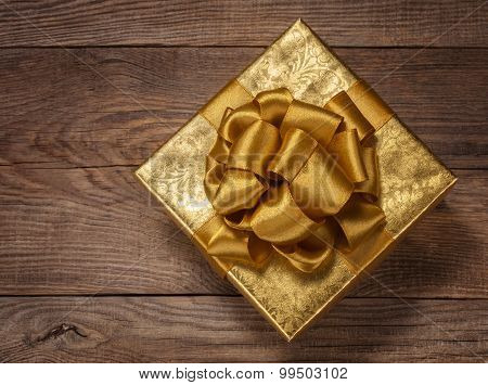 Beautiful Gold Gift Box With A Bow On The Board