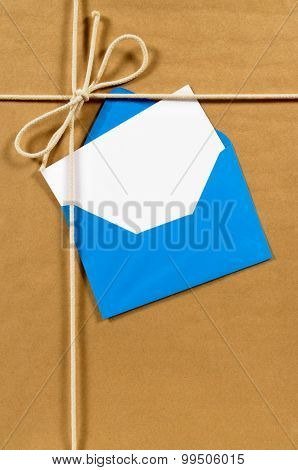 Brown paper parcel with blue envelope and blank message card poster