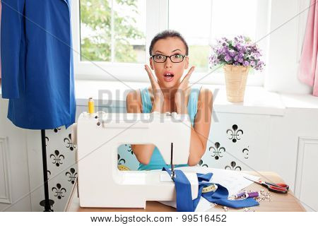 Cheerful young female tailor is expressing surprise