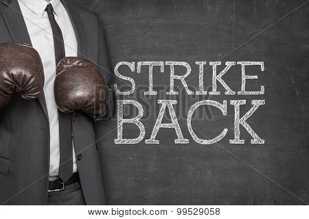 Strike back on blackboard with businessman on side