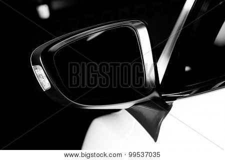 Modern luxury car wing mirror close-up. Expensive, sports auto. Black and white