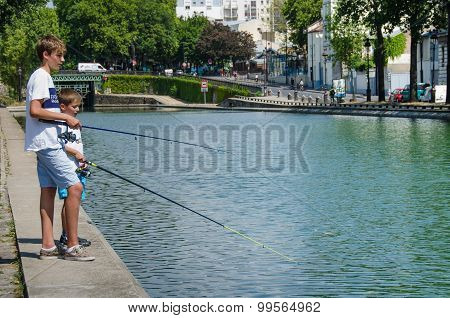 Two boys are fishing in the Canal Saint-Martin in Paris, France