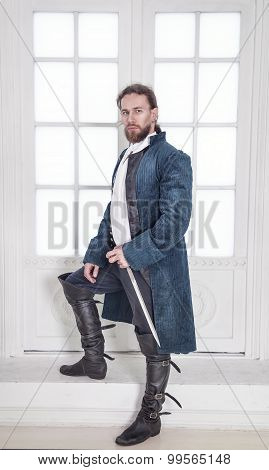 Young Handsome Man In Medieval Clothes With Sword Standing